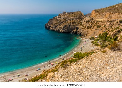 The turquoise sea laps the shore at Rijana Beach, Spain in summertime