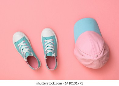 Turquoise shoes and turquoise cap on a pink background. Sport style. Flat lay. The view from the top.