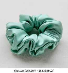 turquoise silk Scrunchy isolated on white background. Flat lay Hairdressing tool of Colorful Elastic Hair Band, Bobble Scrunchy Hairband
