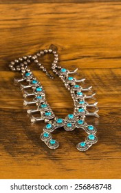 Turquoise and silver Native American Squash Blossom against rustic and marred old wooden boards.