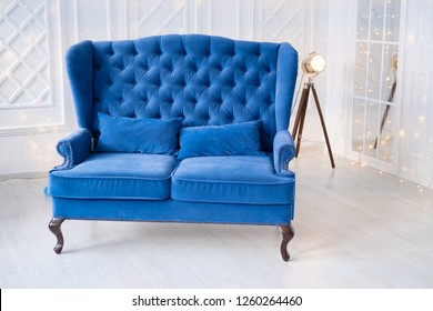 turquoise sofa vintage blue couch in white interior. Old spotlight and Christmas lights
