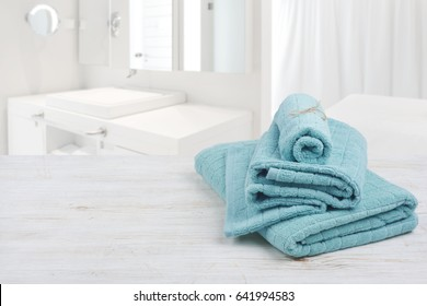 Turquoise spa towels on wooden surface over blurred bathroom background