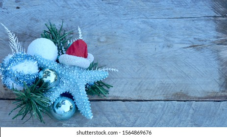 turquoise starfish with red Santa Claus hat laying on a pine branch with christmas bulbs on a natural wood background with copy space