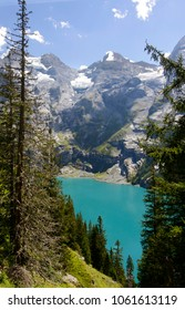 A turquoise tarn in the Swiss alps surrounded by a forest and a rockface