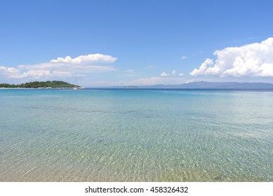 Turquoise transparent waters of a beautiful white sandy Xenia beach in Kassandra, Halkidiki, Greece, on a sunny summer day. Blue sky and sea.