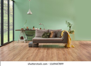 turquoise wall and living room. Grey sofa with yellow blanket and vase of flowers. Study table is on the  back of sofa and decorative white lamp. empty area for carpet.