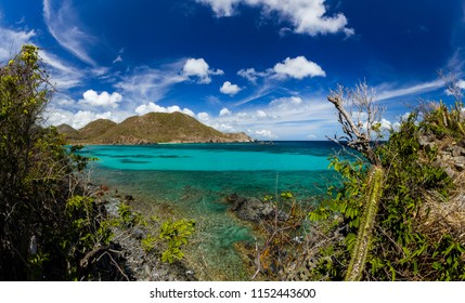 Turquoise water in the bay, crystal clear, peaceful. Gulf of Anse Marcel on St. Martin in the Caribbean. Place for holidays and recreation. The hills and the sky full of clouds are beautiful.