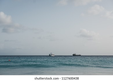 Turquoise water and cloudy sky in Carlisle Bay in Bridgetown, Barbados, two unidentified boats on the horizon.