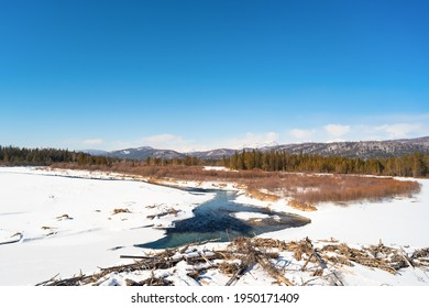 Turquoise water flows among the white snows against the backdrop of the mountains. This is the Irkut River in the reserved Tunkinskaya Valley on a sunny day in early spring. Republic of Buryatia - Shutterstock ID 1950171409