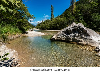 Turquoise water of the french Drome river running between pebbly river banks and green forest with high mountains on the background.