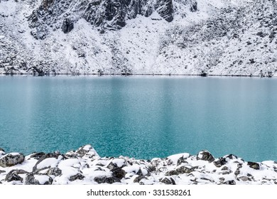 Turquoise water of Gokyo mountain lake and rocks covered with snow on its shore,  Everest region, Nepal
