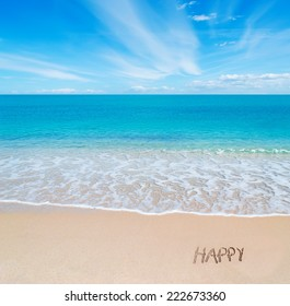 """turquoise water and golden sand in Sardinia with """"happy"""" written in the sand on a cloudy day"""