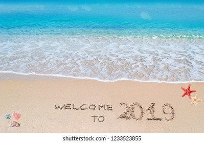 """turquoise water and golden sand with shells and sea stars with """"welcome to 2019"""" written on it"""