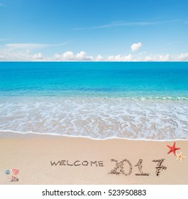 """turquoise water and golden sand with shells and sea stars with """"welcome 2017"""" written on it"""