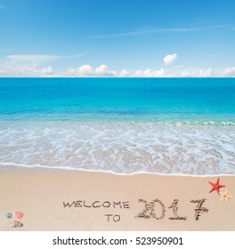 """turquoise water and golden sand with shells and sea stars with """"welcome to 2017"""" written on it"""