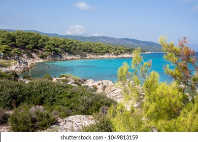 Turquoise water in Greece with mountains full of vegetation