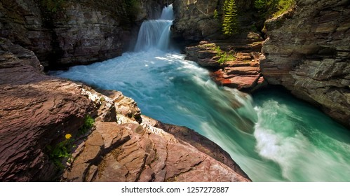 Turquoise water rushes through rocky canyon in a remote waterfall in Glacier National Park, Montana