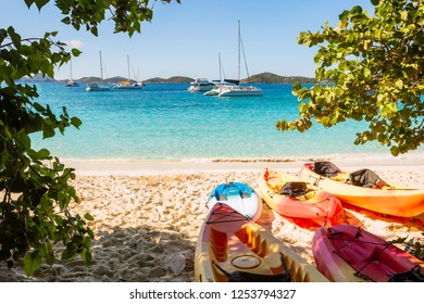 Turquoise water tropical beach. White sand, blue sky, kayaks and boats. St John US Virgin Islands in Caribbean