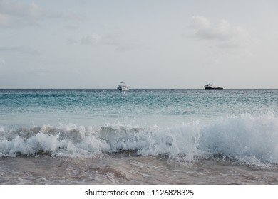 Turquoise water, white sand and waves in Carlisle Bay in Bridgetown, Barbados, two unidentified boats on the horizon.