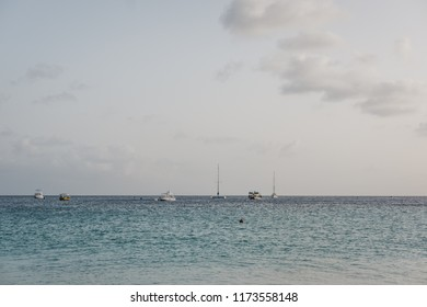 Turquoise water, white sand and waves in Carlisle Bay in Bridgetown, Barbados, unidentified boats on the horizon.