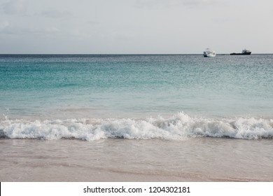 Turquoise water, white sand and waves in Carlisle Bay in Bridgetown, Barbados, at dusk, two unidentified boats on the horizon.