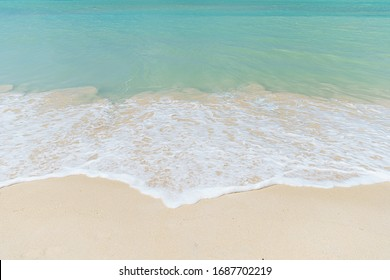 Turquoise waves lap over the fine sands on a Caribbean beach.