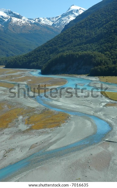 Turquoise winding river, green forest, snowy mountains and blue sky landscape. Dart river valley, Queenstown, New Zealand.