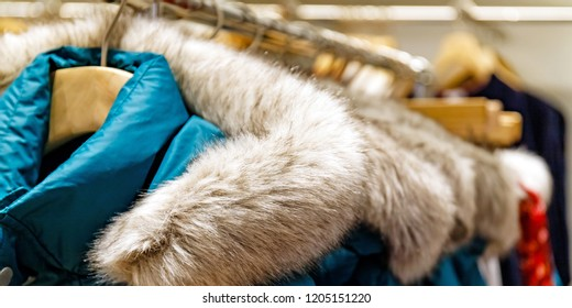 Turquoise winter jackets with fur collar hang on wooden hangers. New collection of winter jackets. Winter season fashion background