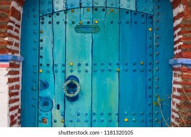 Turquoise wooden rustic doorway in Chefchaouen in Morocco