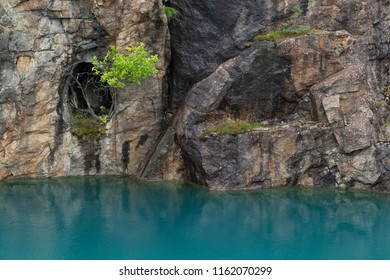 Turquoise-colored waterfront in an old copper mine near Salo, Finland.
