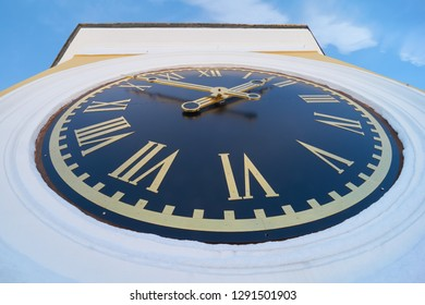 Turret clock with roman numerals on blue clock face. Bell tower of the Epiphany Cathedral in the Monastery of Nilo-Stolobenskaya Pustyn, Tver oblast, Russia