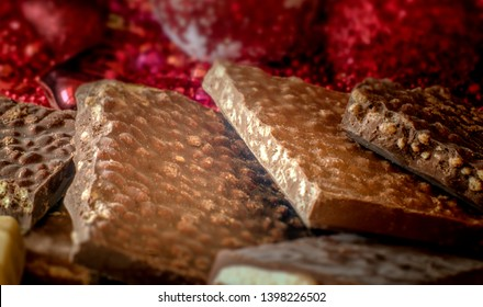 Turron. Festive sweets. Warm sunlight. Selective focus. Blurred background. Traditional Spanish Christmas candy. Torrone and nougat with nuts. Christmas tree decorations in the background.