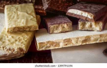 Turron. Festive sweets. Warm sunlight. Selective focus. Blurred background. Traditional Spanish Christmas candy. Torrone and nougat with nuts. Texture, layers.