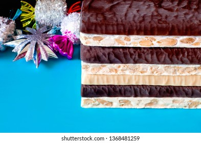 Turron. Traditional Spanish Christmas candy. Turrone and nougat with nuts. Texture, layers, background. Christmas tree decorations in the background.