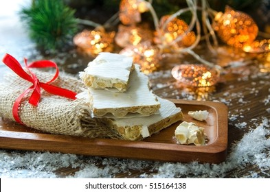 Turron, traditional Spanish sweet for Christmas. Almond nougat dessert served in wooden plate on dark background with snow and fir tree.