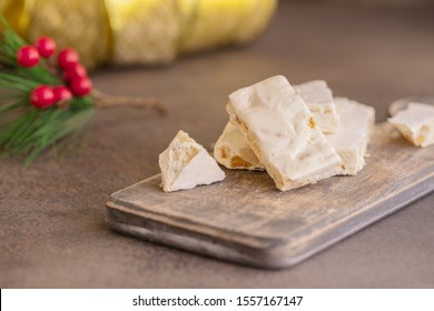 Turron, typical Christmas sweet in Spain. Almond nougat on dark wooden background with Christmas decoration