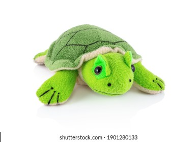 Turtle plushie doll isolated on white background with shadow reflection. Plush stuffed puppet on white backdrop. Fluffy turtle toy for children. Cute furry animal plaything for kids. Green reptile.