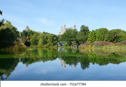 Turtle Pond in Central Park, surrounded by trees and lush marginal plants reflected in the water.