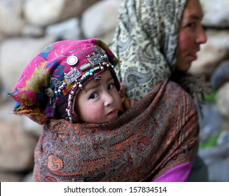 TURTUK, INDIA - JUNE 13: An unidentified Balti woman with her son Sulim, age 3, poses for a photo during Turtuk festival on June 13, 2012 in Turtuk Village, Ladakh, India.