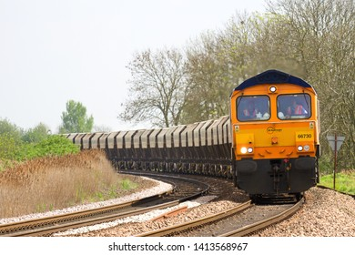 TURVES, CAMBRIDGESHIRE, UK - APRIL 30, 2014: GBRf Class 66/7 No. 66730 'Whitemoor' rounds the curve at Silt Drove in March, in charge of the 6E88 12:39 Middleton Towers to Goole Glassworks working.