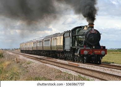 TURVES, CAMBRIDGESHIRE, UK - JULY 19, 2008: GWR Steam Locomotive 4-6-0 Hall Class No. 4936 'Kinlet Hall' powers across the open Fenland landscape with 'The Burton Mail' special charter to Ely.
