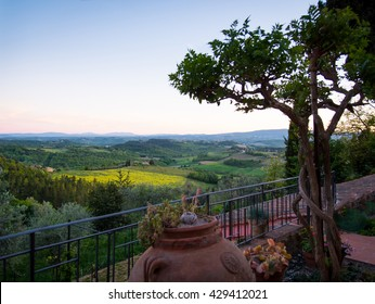 Tuscan balcony overlooking the rolling hills of Tuscany Toscana at sunset.  The village of San Gimingnano visible in the distance.