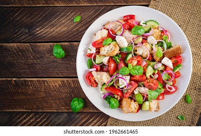Tuscan Panzanella, traditional Italian salad with tomatoes and bread on wooden background. Vegetarian panzanella salad. Mediterranean healthy food. Top view, flat lay