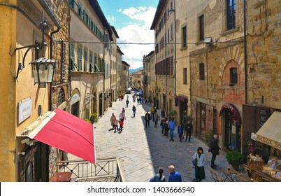 TUSCANY, AREZZO 25.04.2019. Crowd of people on old narrow street in historical center of Arezzo with facade of medieval buildings. Italy