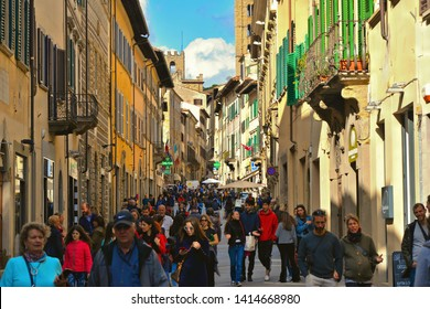 TUSCANY, AREZZO 25.04.2019. Crowd of people on old narrow street in historical centerof Arezzo with facade of medieval buildings. Italy