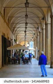 TUSCANY, AREZZO 25.04.2019. tourists relaxing on outdoor restaurant tables in the Piazza grande under Vasari loggias (Loggia di Vasari) in historical center of Arezzo.