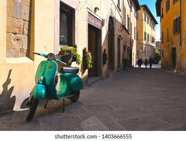 TUSCANY, AREZZO 25.04.2019. Vintage green Vespa Piaggio scooter in old narrow street in historical center of Arezzo with facade of medieval buildings and people in background. Italy