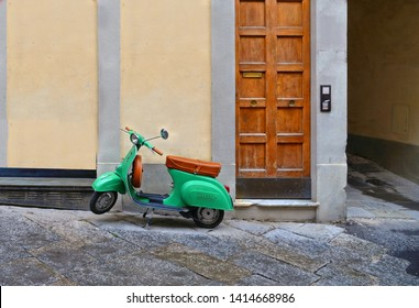 TUSCANY, AREZZO 25.04.2019. Vintage green Vespa Piaggio scooter in old narrow street in historical center of Arezzo with facade of medieval buildings in background. Italy