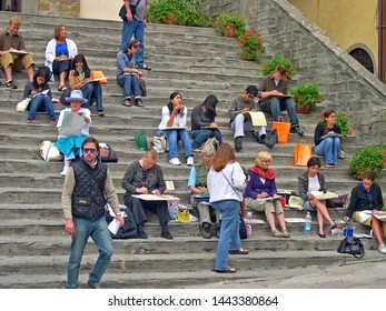 TUSCANY, CORTONA – SEPTEMBER 19, 2006: tourists painting and relaxing in Piazza della Repubblica. The square is the heart of Cortona.