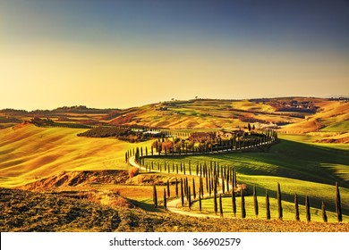 Tuscany, Crete Senesi rural sunset landscape. Countryside farm, cypresses trees, green field, sun light and cloud. Italy, Europe.
